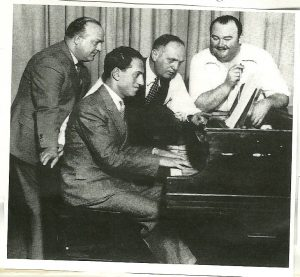 "George Gershwin at the piano. Left to right: Ferde Grofé, S.L> Rothafel (""Roxy""), and Paul Whiteman at the Roxy Theatre, New York."
